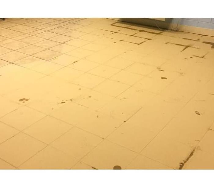 Tile flooring covered in yellow mud